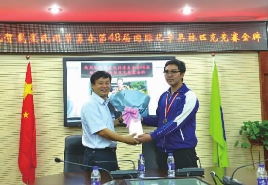 8月3日,湖南师大附中校长谢永红(左)为在第48届国际中学生化学奥林匹克竞赛中获得金牌的戴昱民同学送上祝福和鲜花。